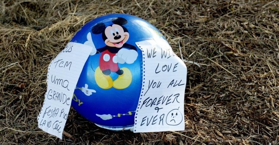16.dez.2012 - Na cidade de Newtown (Connecticut), bola infantil é colocada em gramado com mensagens em inglês e português