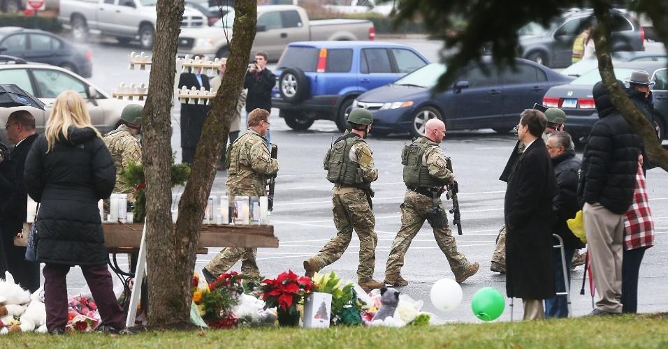 16.dez.2012 - Policiais do Estado de Connecticut andam armados pelos arredores da escolar Sandy Hook, em Newtown, Connecticut, depois que uma igreja que fica próxima ao local foi evacuada por ameaça de bomba neste domingo (16). A escola foi palco do massacre de 26 pessoas, entre elas 20 crianças, por um atirador na sexta-feira.