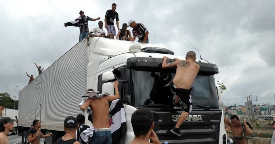 16.dez.2012 - Torcedores corintianos sobem em caminhão na Marginal Tietê para comemorar título mundial