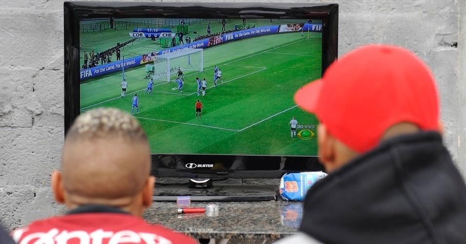 Corintianos acompanham jogo na Comunidade da Paz, em Itaquera, que deve dar lugar a obras do Itaquerão