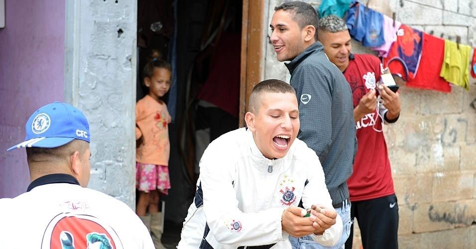 Dono da TV, David acende uma bombinha para comemorar gol do Corinthians na Comunidade da Paz