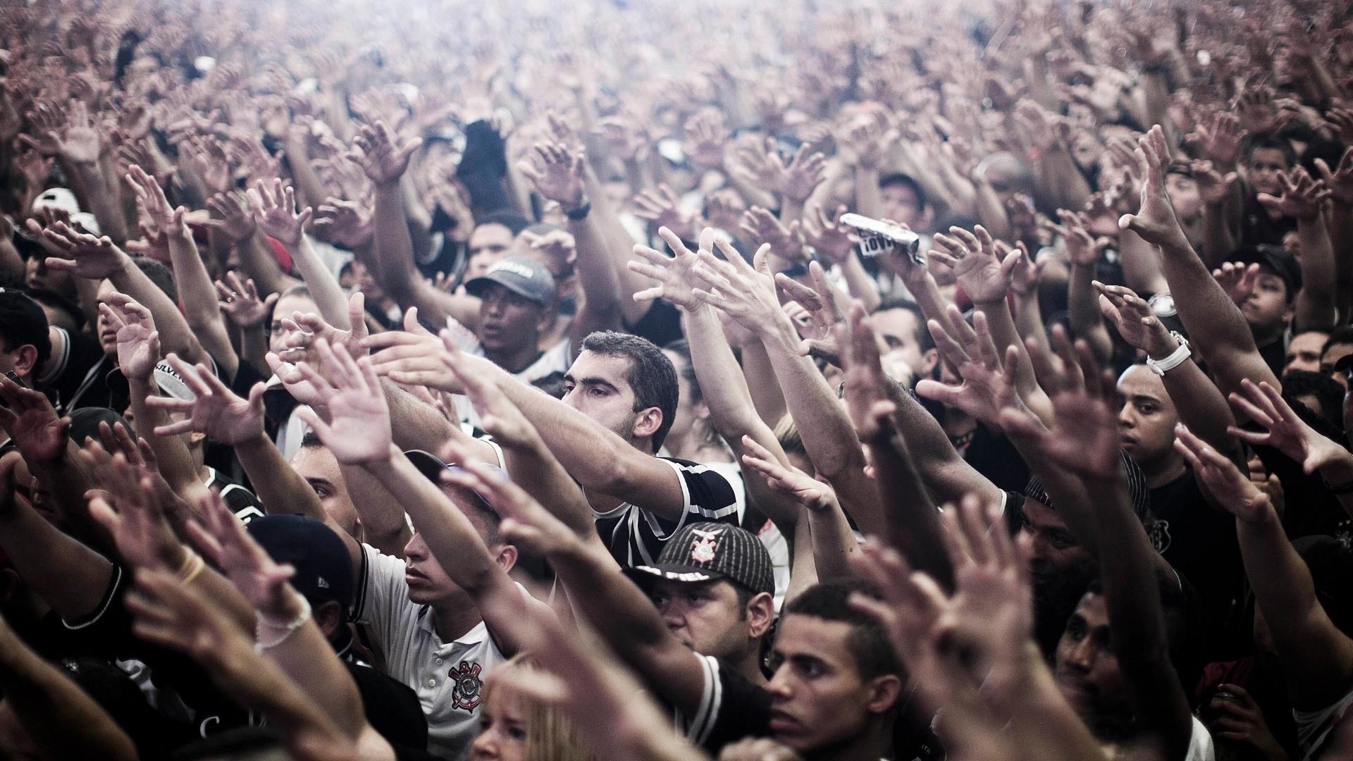 Torcedores corintianos levantam as mãos para