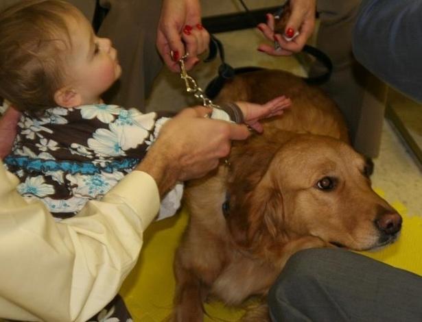 16.dez.2012 - Criança brinca com cachorro da raça golden retriever, na igreja luterana da cidade de Newtown (EUA). Os cães, do projeto da Igreja Luterana de Illinois