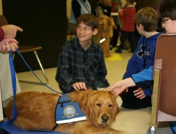 16.dez.2012 - Crianças da cidade de Newtown (EUA) brincam com cães da raça golden retriever na igreja luterana da cidade. Os cães, do projeto da Igreja Luterana de Illinois