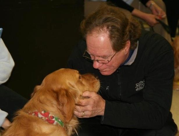 16.dez.2012 - Homem brinca com cão da raça golden retriever na igreja luterana da cidade de Newtown (EUA). Os cães, do projeto da Igreja Luterana de Illinois