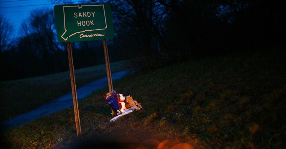 17.dez.2012 - Animais de pelúcia são colocados em placa que sinaliza o vilarejo de Sandy Hook, em Newtown, Connecticut, nesta segunda-feira. Hoje ocorreram dois funerais de vítimas do massacre que aconteceu em uma escola primária da cidade, resultando em 26 mortes, entre elas de 20 crianças