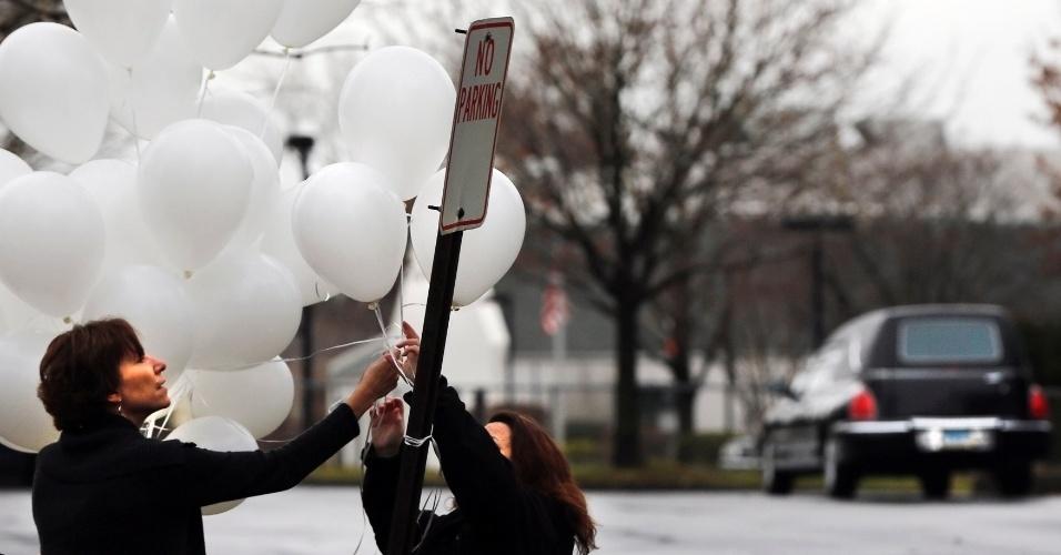 17.dez.2012 - Mulheres penduram balões fora do Abraham L. Green & Sons Funeral Home, onde o funeral de Noah Pozner, 6, vítima do massacre da Escola Primária Sandy Hook foi realizado
