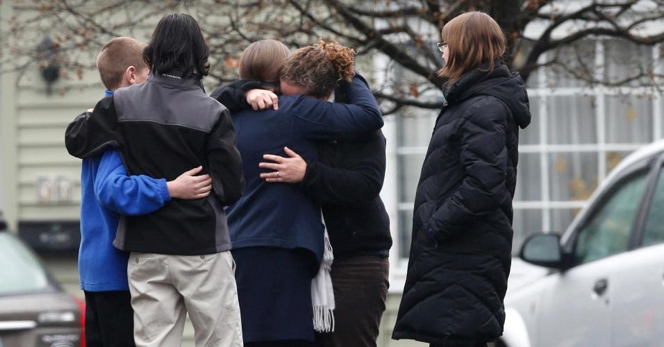 17.dez.2012 - Pessoas se abraçam ao deixar a Casa Funerária Honan, onde a família de Jack Pinto, de seis anos de idade, realiza seu funeral, em Newtown, em Connecticut