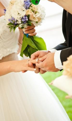 Imagem de noivo colocando a aliança no dedo da noiva