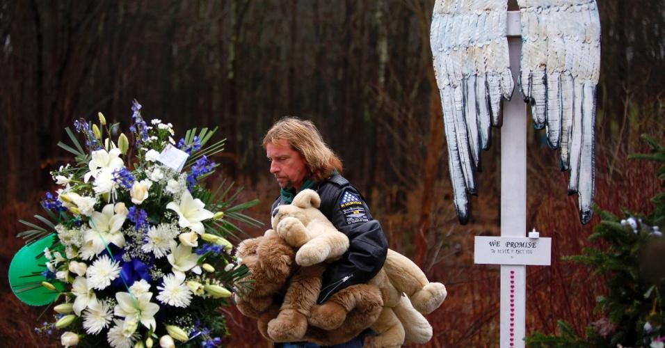 18.dez.2012 - Homem segura ursos de pelúcia em um memorial improvisado em homenagem às vítimas do massacre que matou 27 pessoas, incluindo o atirador, na Escola Primária Sandy Hook, na última sexta-feira (14), em Connecticut, Estados Unidos