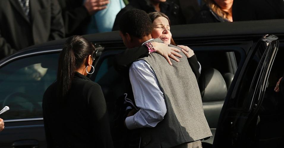 18.dez.2012 - Krista Rekos, mãe de Jessica Rekos, vítima do massacre da Escola Primária Sandy Hook, abraça um rapaz após o funeral de sua filha, realizado na igreja Saint Rose Lima, em Newtown, Connecticut, nesta terça-feira (14)