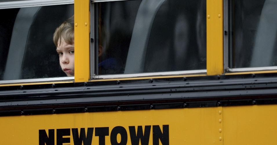 18.dez.2012 - Menino olha pela janela do ônibus escolar estacionado próximo à igreja Saint Rose Lima, em Newtown, Connecticut, onde é realizado o funeral de uma das vítimas do tiroteio da Escola Primária Sandy Hook, que ocorreu na última sexta-feira (14)