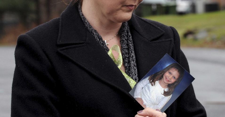 18.dez.2012 - Mulher segura a fotografia de Jessica Rekos, 6, uma das vítimas do tiroteio na Escola Primária Sandy Hook, cujo funeral é realizado na igreja Saint Rose Lima, em Newtown, Connecticut, nesta terça-feira (18)