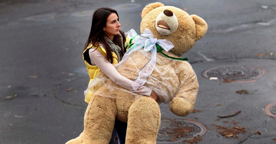 18.dez.2012 - Mulher segura um urso de pelúcia enquanto caminha em direção ao memorial improvisado construído em homenagem às vítimas do massacre que matou 27 pessoas, incluindo o atirador, na Escola Primária Sandy Hook, na última sexta-feira (14), em Connecticut, Estados Unidos