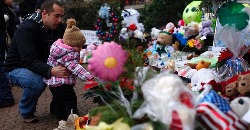 18.dez.2012 - Homem e criança olham para um memorial improvisado em homenagem às vítimas do massacre que matou 27 pessoas, incluindo o atirador, na Escola Primária Sandy Hook, na última sexta-feira (14), em Connecticut, Estados Unidos
