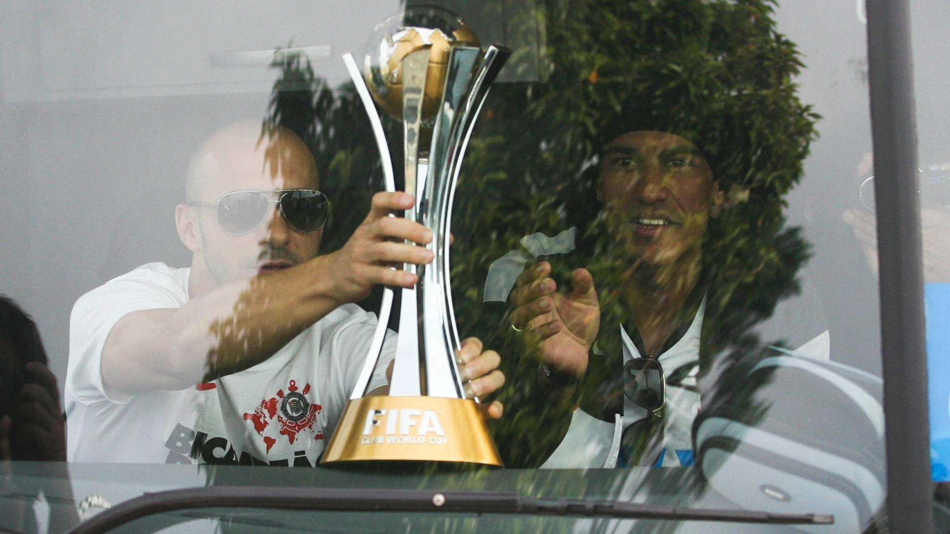 18.dez.2012- Alessandro apoia taça de campeão mundial no painel do ônibus para exibi-la aos torcedores na saída do aeroporto de Guarulhos, em São Paulo