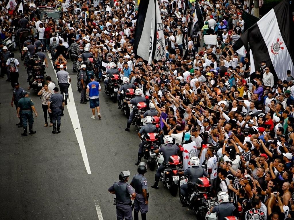 18.dez.2012- Barrados por escolta policial, torcedores corintianos tentam tirar fotos do trio elétrico com os jogadores