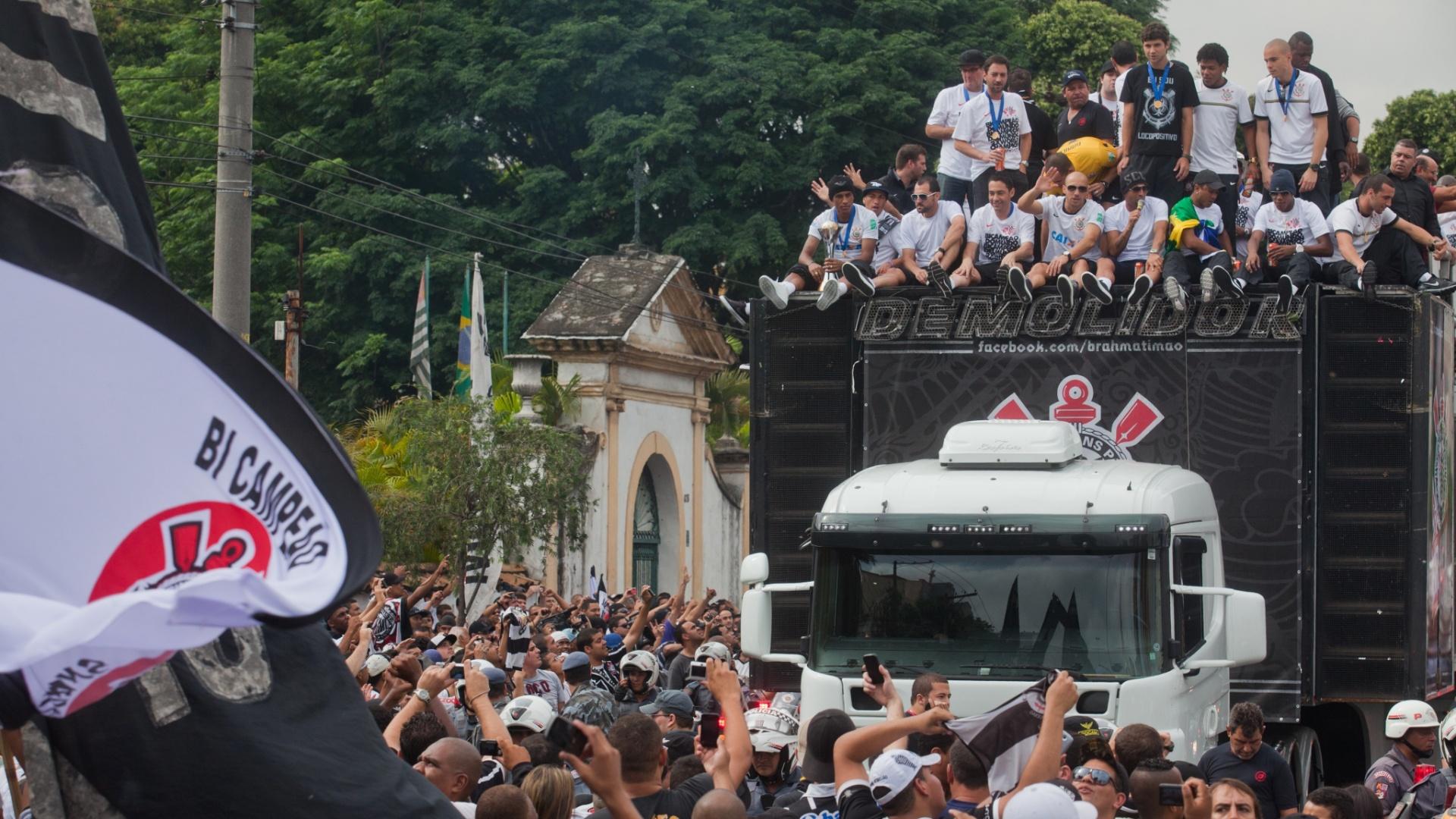 18.dez.2012- Rodeado por torcedores, trio elétrico com os jogadores do Corinthians passa pelas ruas de São Paulo