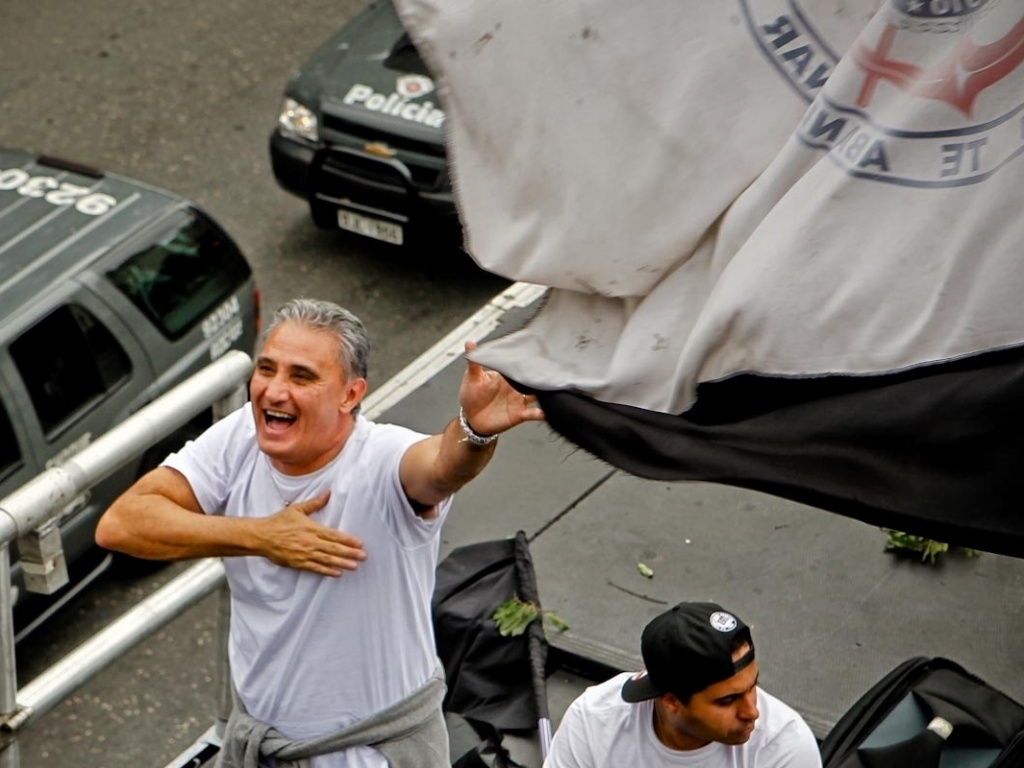 18.dez.2012- Tite sorri e bate no peito comemorando título do Mundial de clubes em passeata pelas ruas de São Paulo