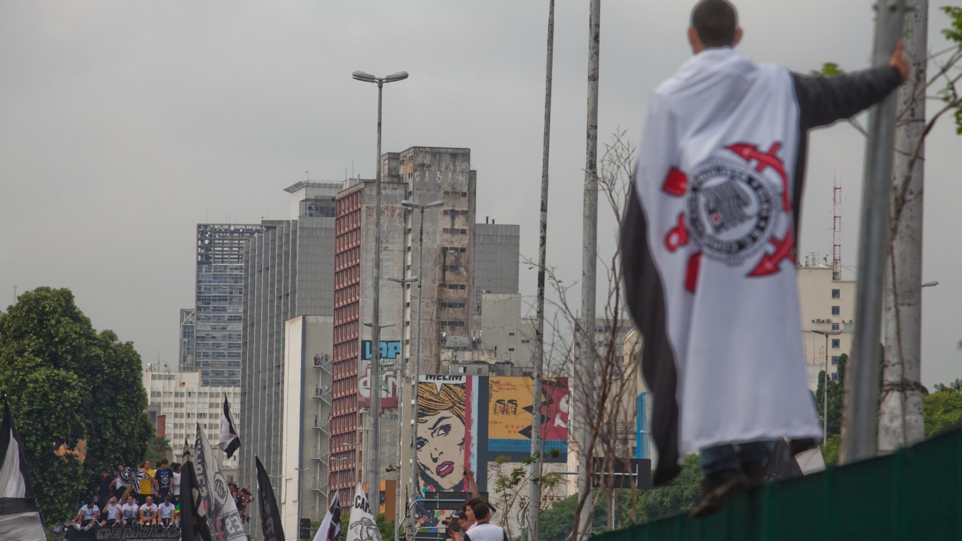 18.dez.2012- Torcedor sobe em grade para observer comemoração de título mundial em passagem de tiro elétrico pela Av. Tiradentes em São Paulo