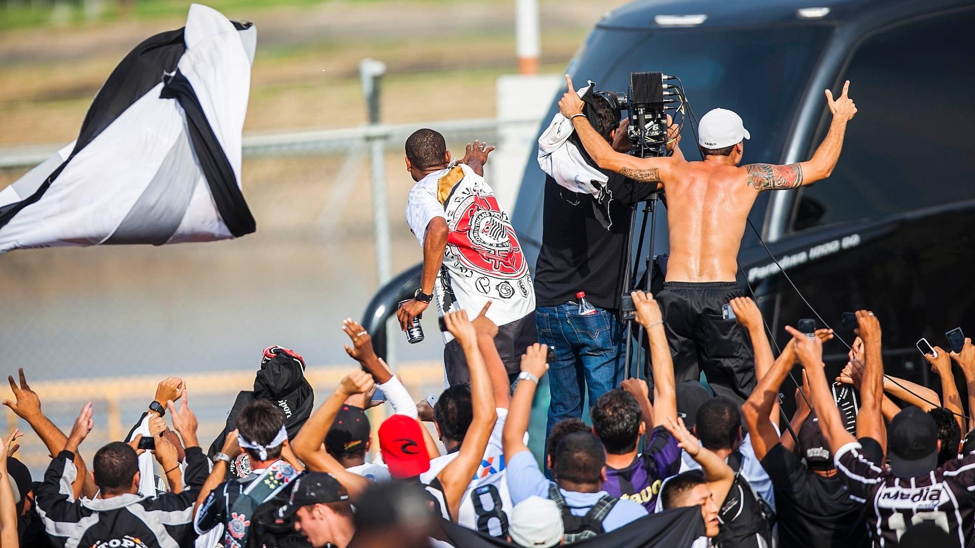 18.dez.2012- Torcedores do Corinthians recepcionam ônibus do time em desembarque no aeroporto de Guarulhos, em São Paulo