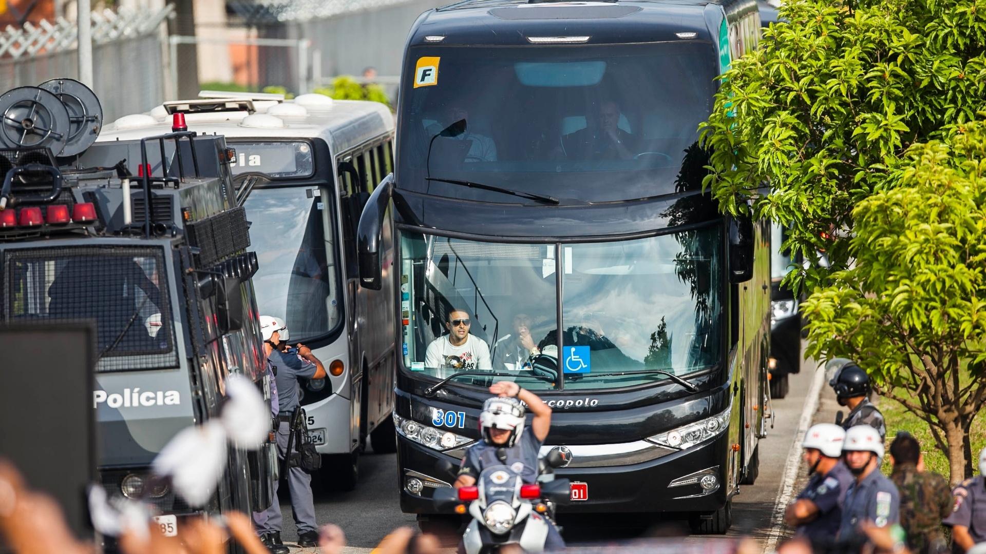 18.dez.2012-Alessandro exibe taça a torcedores pela janela e Corinthians deixa o aeroporto de Guarulhos em ônibus fechado