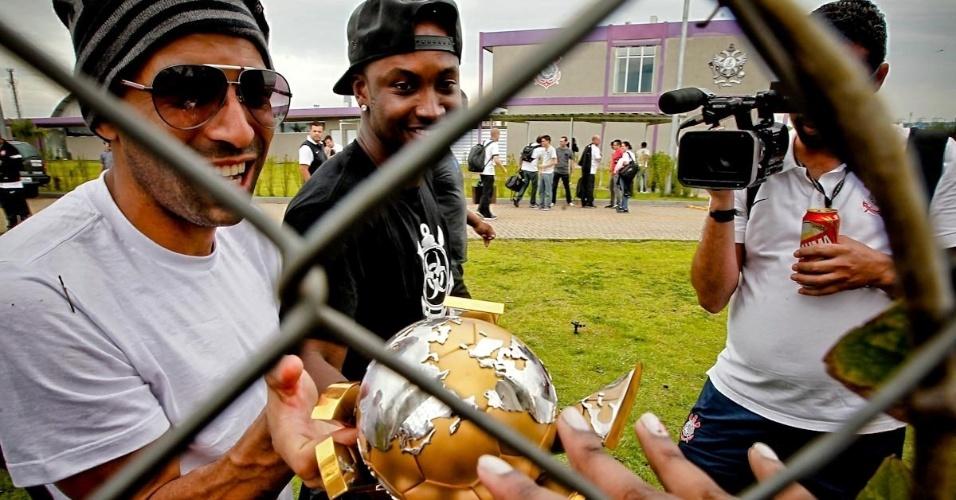 18.dez.2012-Emerson leva troféu de campeão mundial ao alambrado do CT do Corinthians para que os torcedores presentes também pudessem tocar no prêmio