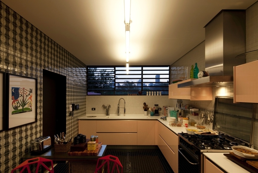 Na cozinha, elementos originais da casa - como o armário - foram combinados a outros moderníssimos como as cadeiras industriais desenhadas por Konstantin Grcic. O revestimento em pastilhas Bico de Jaca (Jatobá) constrasta com os módulos suspensos com acabamento em rosa suave. A Casa do Arquiteto tem projeto de reforma assinado por Marcelo Rosenbaum