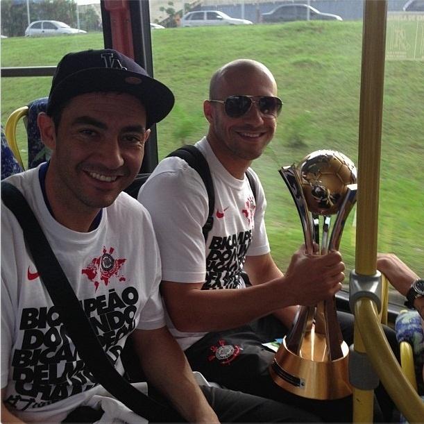 Chicão e Alessandro tiram foto com a taça do Mundial no ônibus após o desembarque no aeroporto de Guarulhos