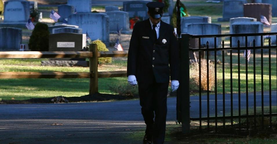 19.dez.2012 - 19.dez.2012 - Um bombeiro deixa o cemitério depois do funeral de Daniel Barden, 7, uma das 20 crianças mortas em tiroteio na escola primária Sandy Hook, em Newtown, Connecticut (EUA), em 14 de dezembro. Os bombeiros da cidade fazem nesta quarta-feira (19) um tributo ao garoto que queria seguir a profissão no futuro