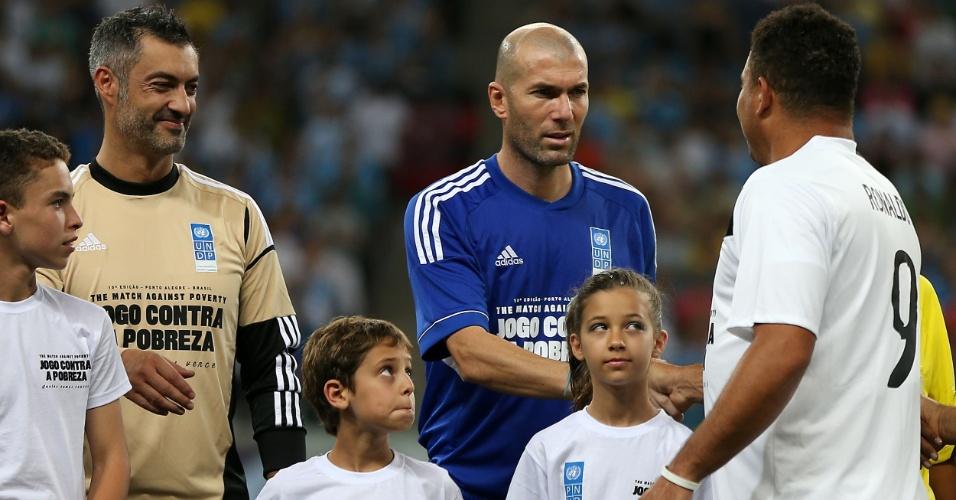 19.dez.2012 - Adversários no amistoso, Ronaldo e Zidane se cumprimentam antes do início do Jogo Contra a Pobreza