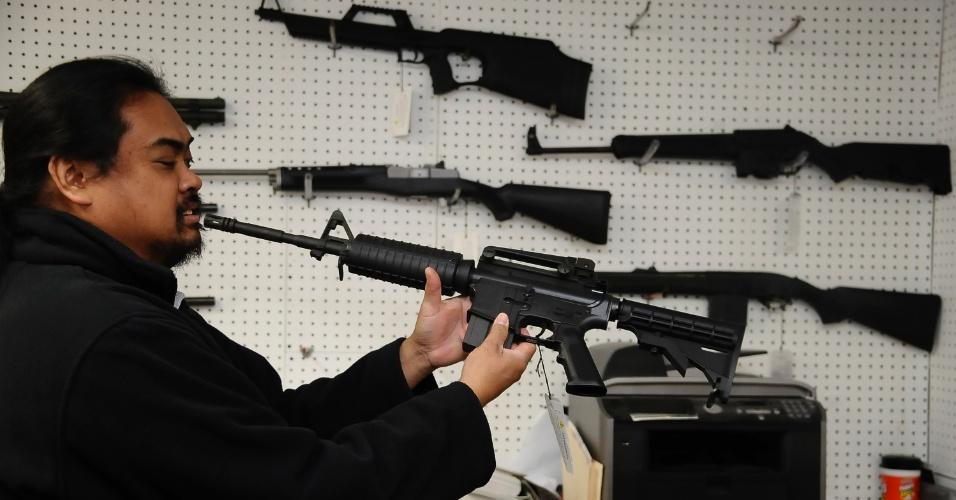 19.dez.2012 - Aristotle Rogel, proprietário de uma loja de armamentos em Burbank, na Califórnia, mostra um rifle semiautomático Umarex Colt M4 e diz que armas como esta estão mais populares desde o dia do massacre da escola primária Sandy Hook, em Connecticut, em 14 de dezembro. A venda de fuzis AR-15, do tipo usado pelo atirador para matar 27 pessoas, entre elas a própria mãe e 20 crianças da escola, aumentou desde então, segundo Rogel