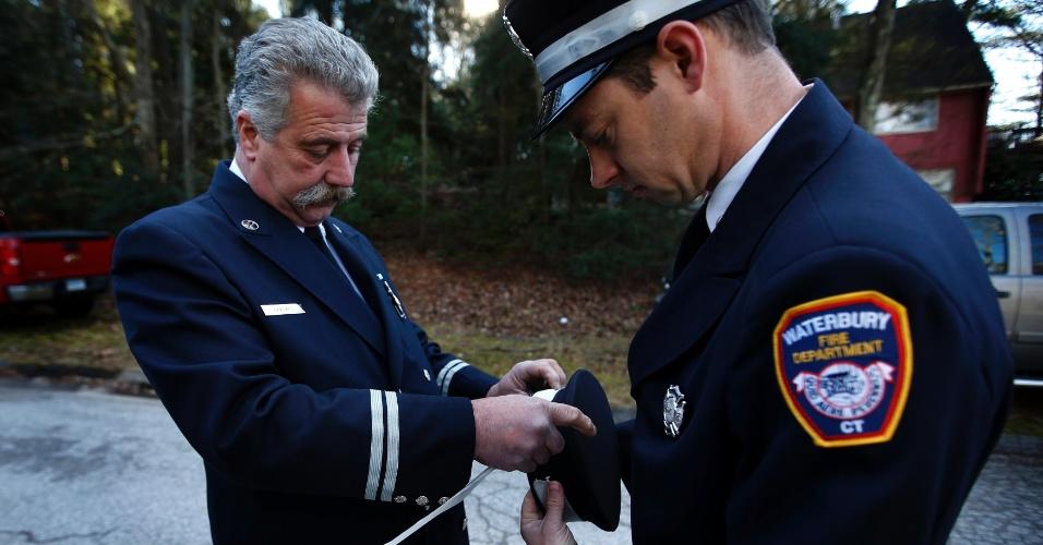 19.dez.2012 - Os bombeiros Gary Leblanc (à esq.) e Dave Morgan amarram fitas brancas em seus chapéus antes do enterro de Daniel Barden, 7, uma das 20 crianças mortas em tiroteio na escola primária Sandy Hook, em Newtown, Connecticut (EUA), em 14 de dezembro. Os bombeiros da cidade fazem um tributo ao garoto que queria seguir a profissão no futuro
