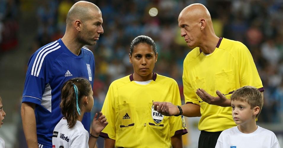 19.dez.2012 - Zidane conversa com Pierluigi Colina antes do início do Jogo Contra a Pobreza