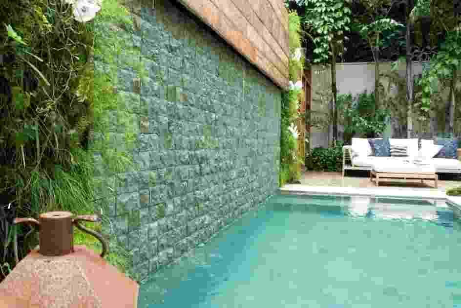 Nessa residência em São Paulo (SP), a cascata que deságua na piscina de borda infinita cai de um painel de madeira e escorre por uma parede revestida com pedras asiáticas azuladas. Ladeando a cascata foram inseridos dois jardins verticais. O projeto é da paisagista Gigi Botelho - Divulgação