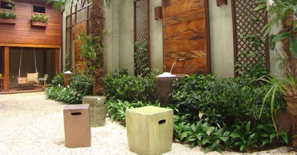 Para esse jardim em São Paulo (SP), a paisagista Gigi Botelho projetou amplos arcos de metal com paineis de madeira. Junto às estruturas, a água sai de bicas metálicas e escorre sobre enormes vasos de cerâmica