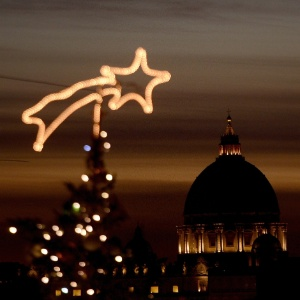 Basílica de São Pedro, no Vaticano, é visto ao fundo de uma árvore de Natal no centro de Roma - Filippo Monteforte/AFP