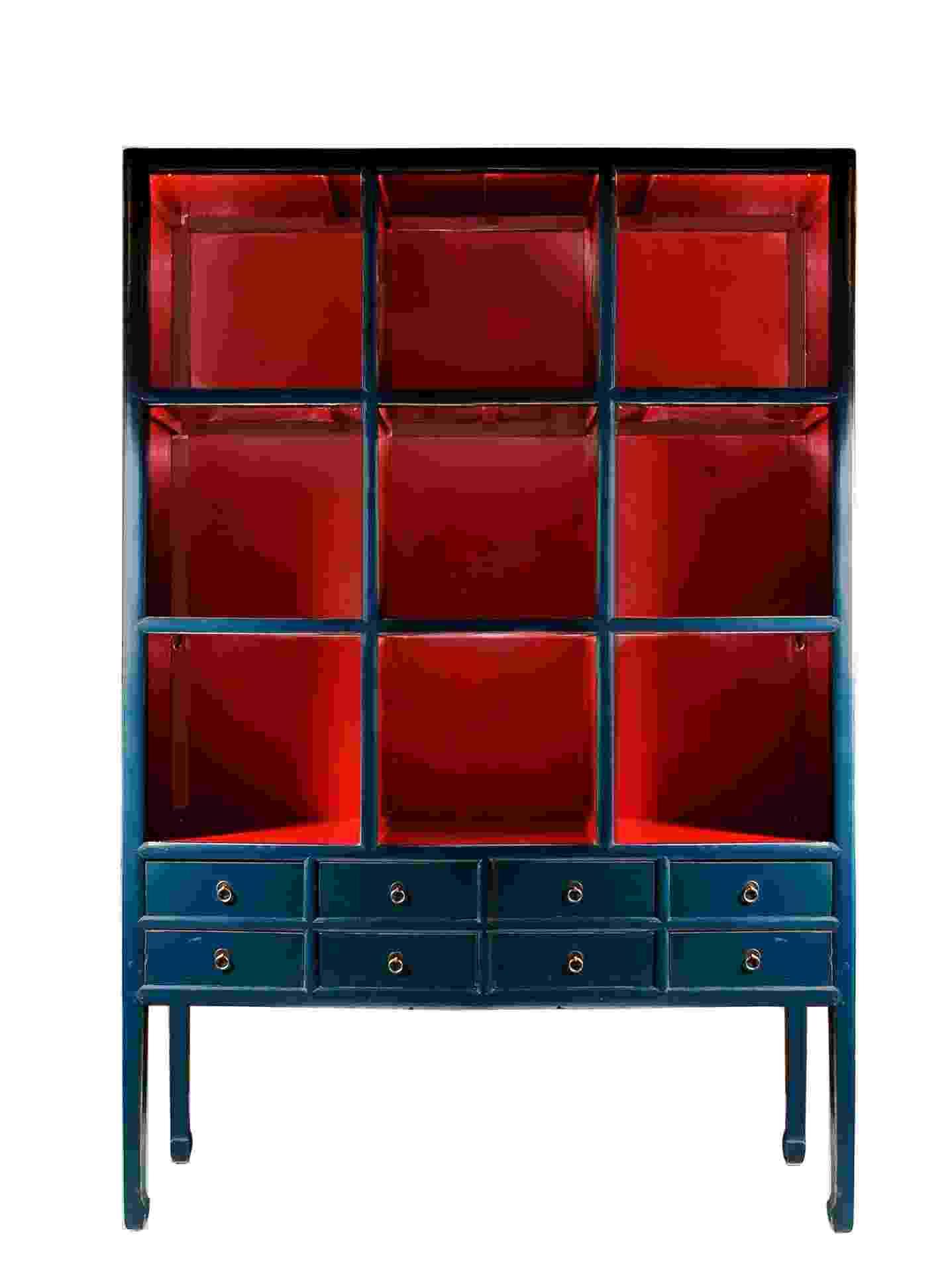 A estante de madeira patinada nas cores azul e vermelho possui pequenas gavetas e mede 150 cm por 46 cm por 230 cm. A peça é importada pela 6F Decorações e vendida na Blue Gardenia por R$ 4.950 I Preços pesquisados em dezembro de 2012 e sujeitos a alterações - Divulgação