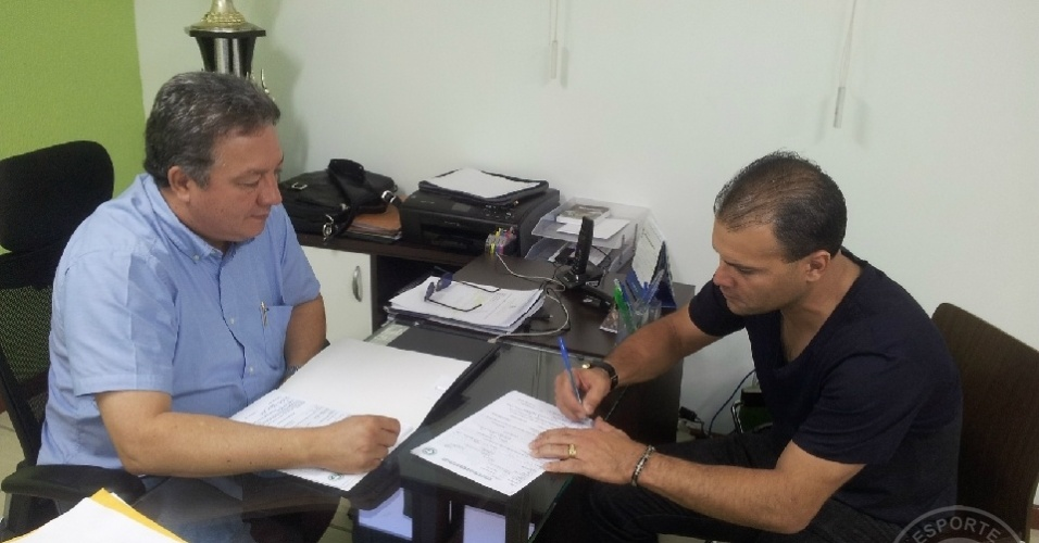 O goleiro Harlei assina seu novo contrato com o Goiás observado por João Bosco Luz