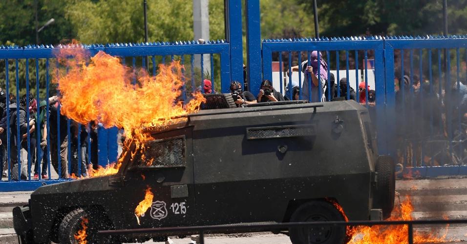 21.dez.2012 - Carro da tropa de choque da polícia chilena pega fogo durante protesto de estudantes; movimento pede reforma educacional no país desde 2011