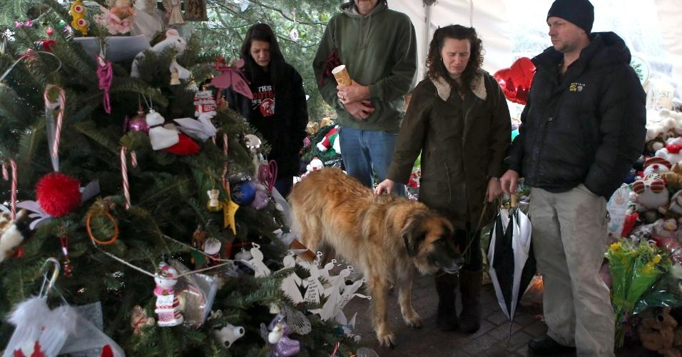 21.dez.2012 - Pessoas fazem um minuto de silêncio em frente a um memorial de flores e objetos deixados em homenagem às vítimas do tiroteio Sandy Hook