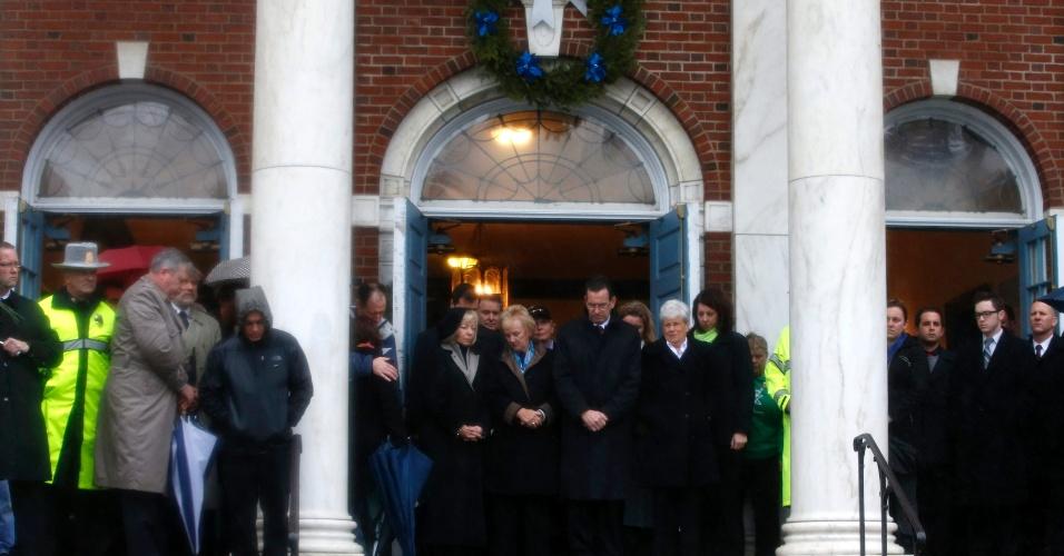 Na porta da Prefeitura de Newtown, o governador de Connecticut (EUA), Daniel Malloy, acompanhado de diversas pessoas, faz um minuto de silêncio em memória das vítimas do tiroteio na escola Sandy Hook, uma semana após o ocorrido