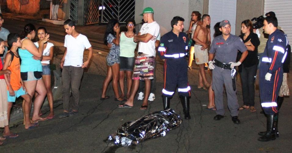 22.dez.2012 - Curiosos observam corpo coberto de menor assassinado a tiros em Guarulhos (SP)