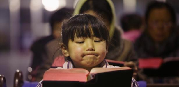 Garota lê a Bíblia em igreja no vilarejo de Gaojiabao, na China