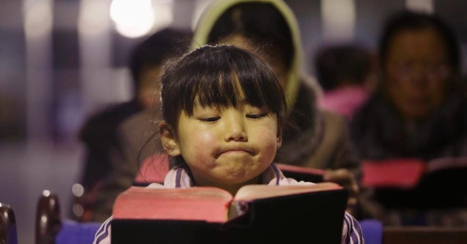 22.dez.2012 - Garota lê a Bíblia em igreja no vilarejo de Gaojiabao, na China