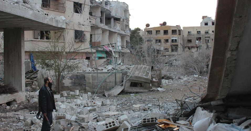 22.dez.2012 - Integrante do Exército Livre Sírio observa imóveis danificados por forças leais ao ditador sírio, Bashar al Assad, em Zamalka, perto de Damasco