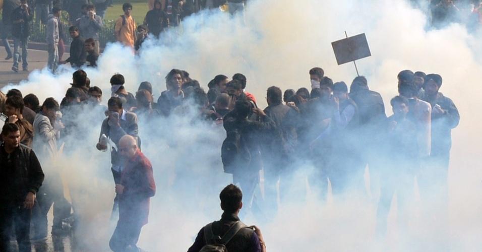 22.dez.2012 - Manifestantes se protegem de gás lacrimogêneo jogado pela polícia durante protesto a favor de uma maior segurança para as mulheres em Nova Déli, capital da Índia. A cidade tem sido palco de uma série de manifestações após o estupro coletivo de uma jovem em um ônibus municipal, no último domingo (16)