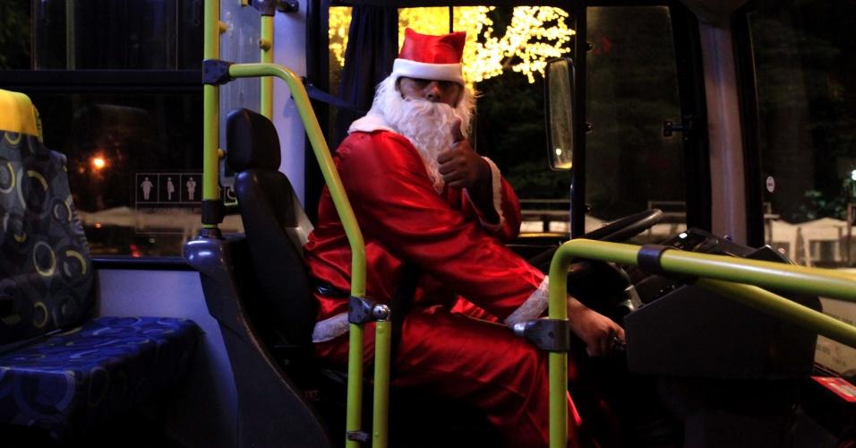 22.dez.2012 - Motorista fantasiado de Papai Noel dirige ônibus com decoração especial de Natal na avenida Paulista, em São Paulo