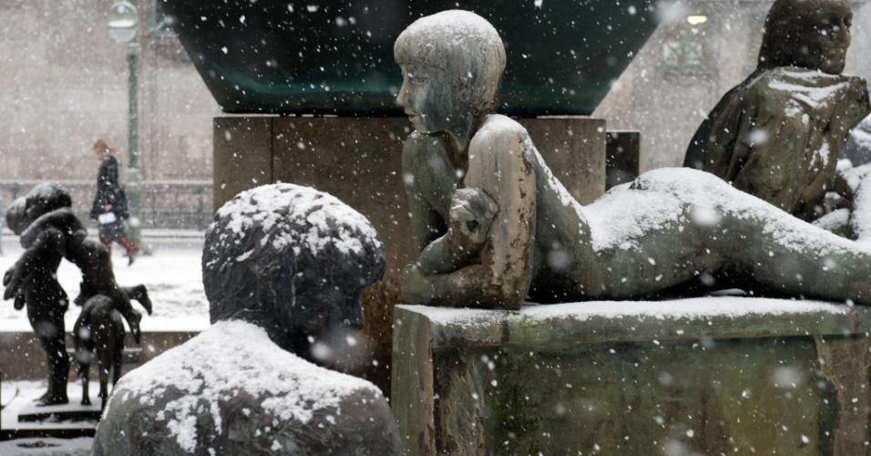 22.dez.2012 - Mulher passa ao lado de fonte coberta com neve em Berlim, na Alemanha