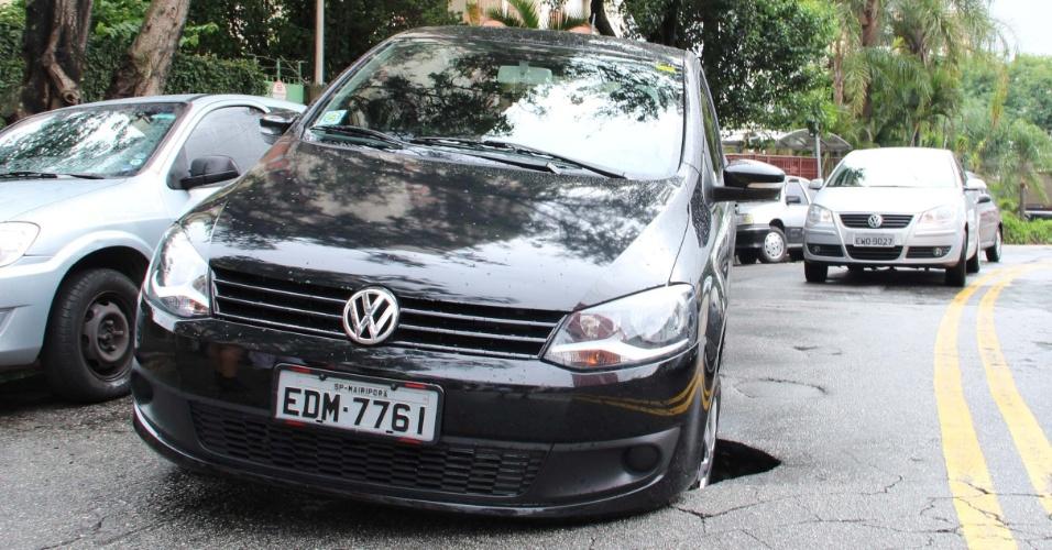 22.dez.2012 - Um grande buraco se abriu embaixo de um veículo de passeio na avenida Guacá, no bairro Lauzane Paulista, zona norte de São Paulo (SP)